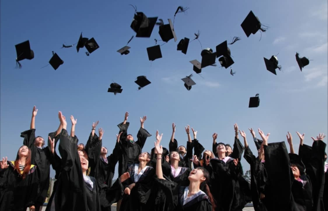 Group of students celebrating graduation at visual communication college in chennai by throwing off their hats