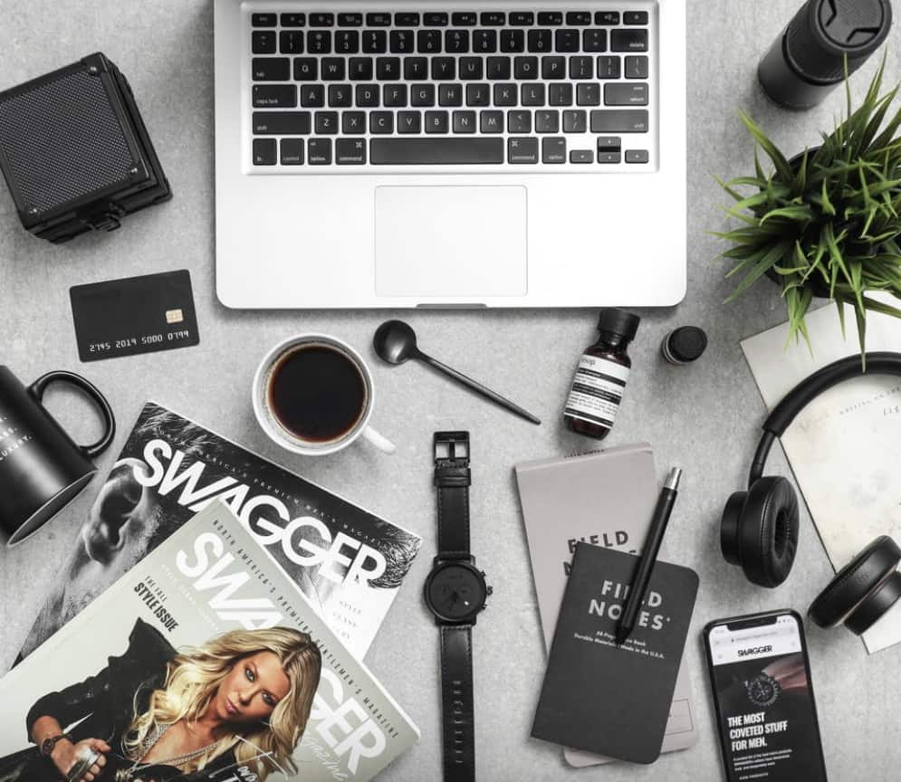 Desk area of a visual communication student displaying modern gadgets along with a plant and coffee