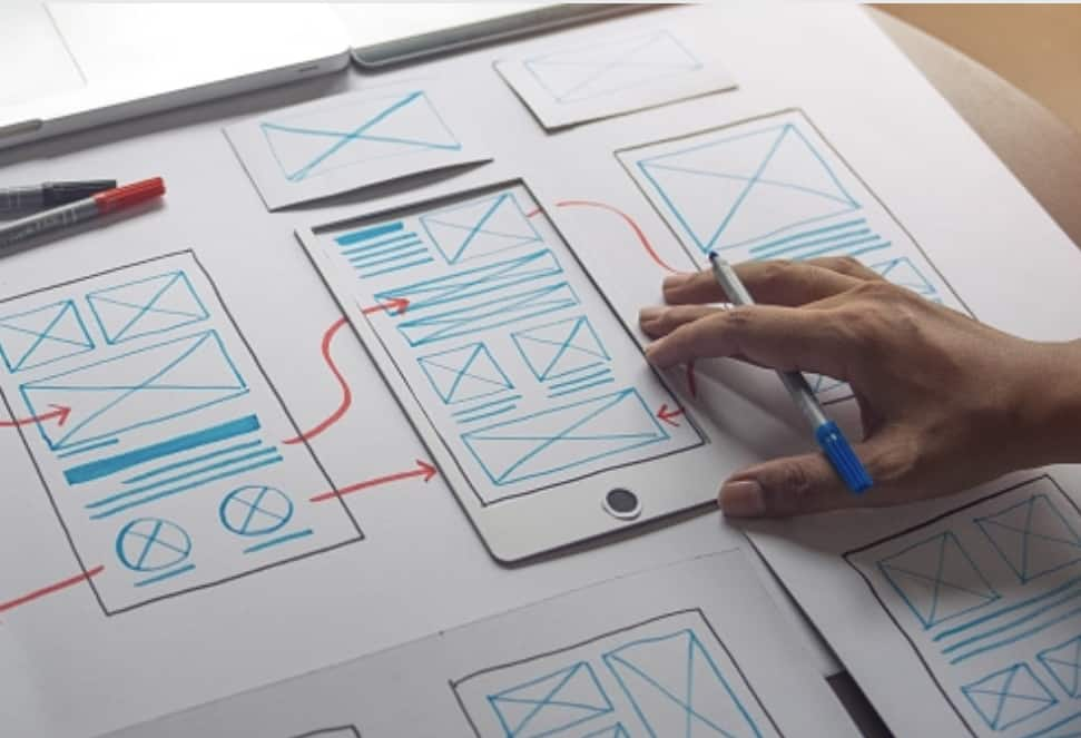 Student hand with pen pursuing visual communication course invloved in web design UX for mobile