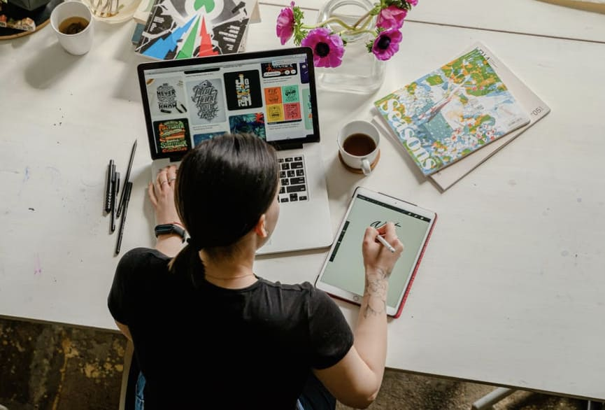 Young design institute graduate working simultaneously with laptop and ipad on a table