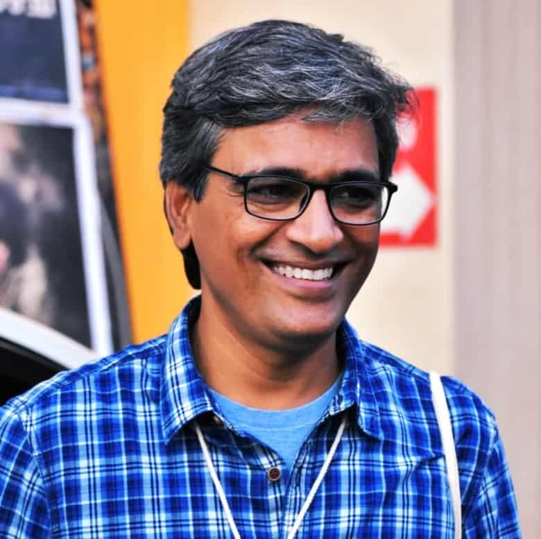 Man in a blue shirt with spectacles and giving a warm smile