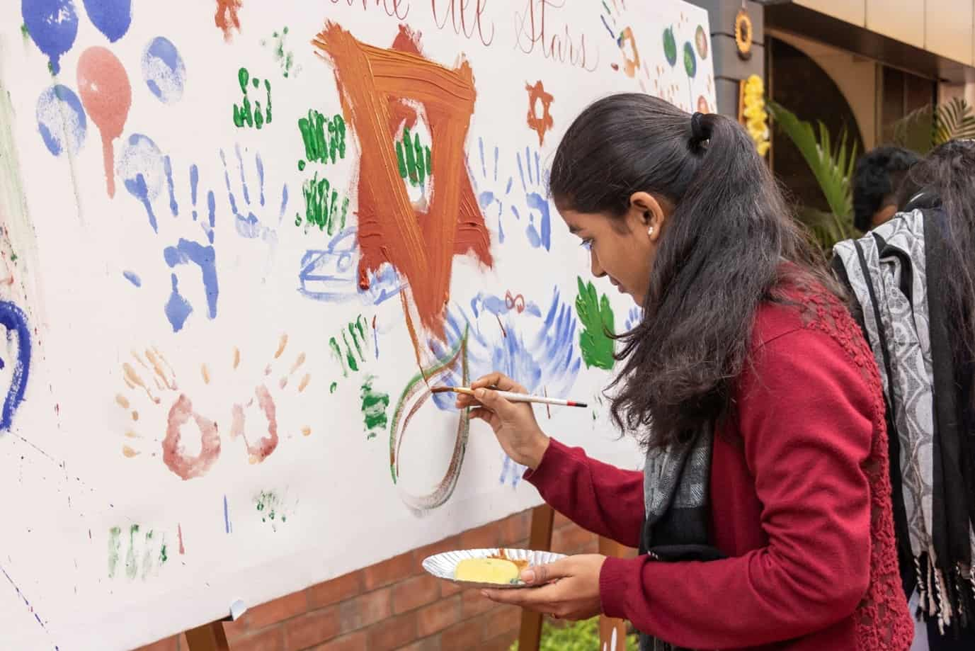 Young student of BFA college in chennai doing calligraphy and art work with color palette and brush on a board