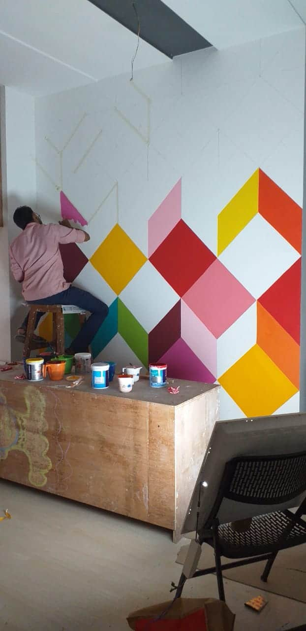 A man standing on the ladder and doing diamond patterns on the wall in different colours during the art workshop organized at our DOT School of Design