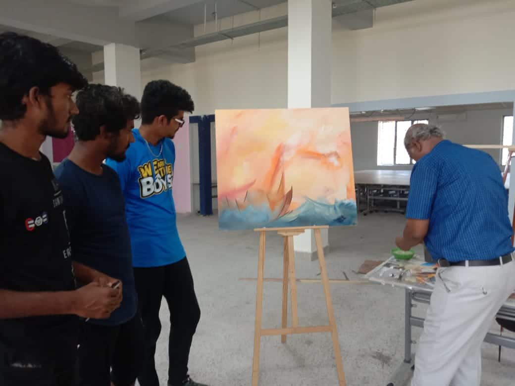 Three students of DOT School of design watching the completed painting of scenary during the art workshop