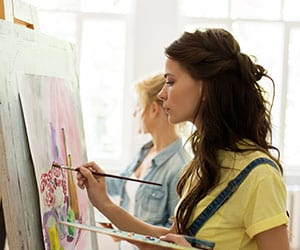 Two students involved in painting with a color palette in hand and a drawing board stand