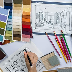 Picture of a living room sketch, color palette, and pencils along with a hand designing an interior plan