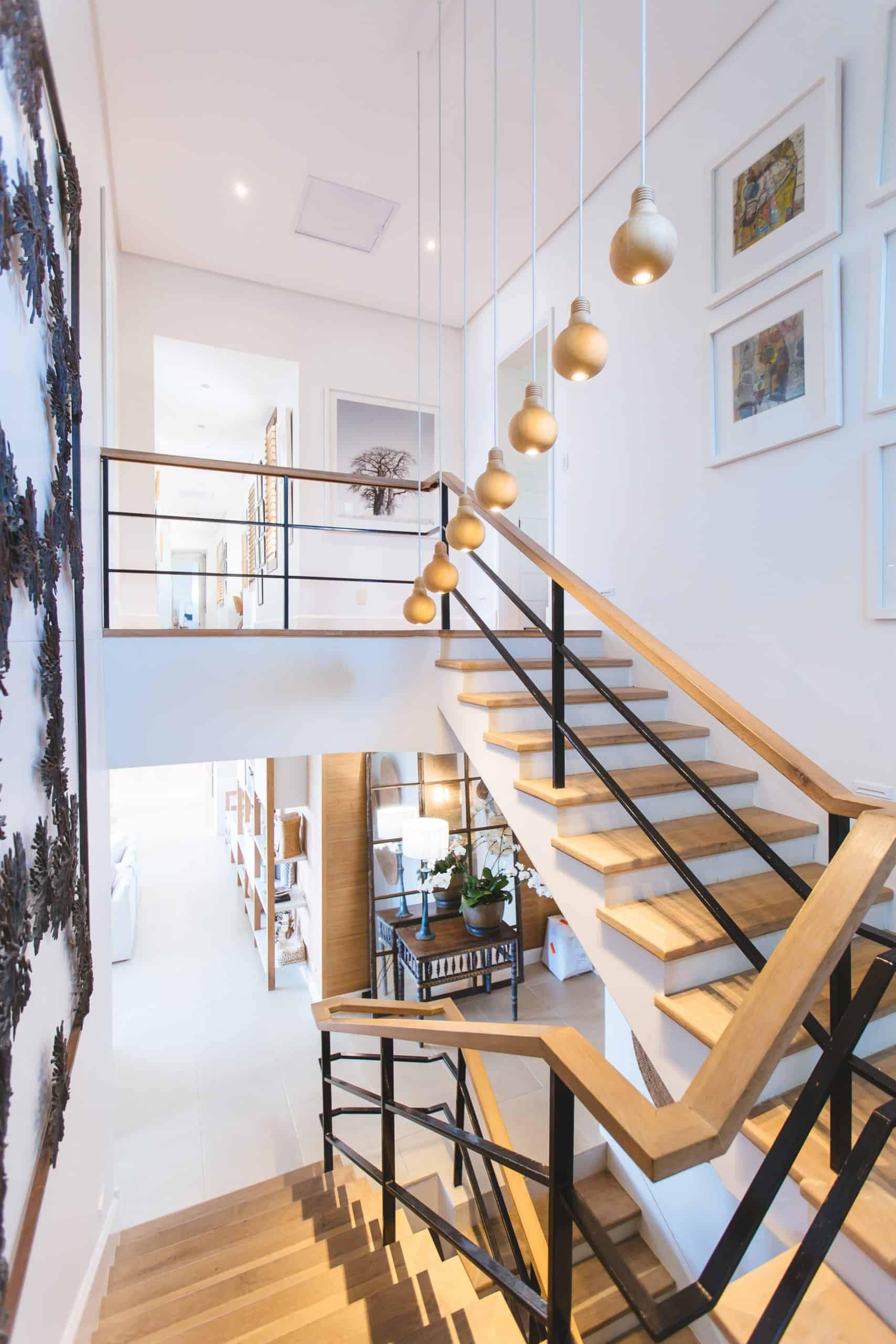 Wooden staircase with railing and white riser with hanging light setup and wall mounted paintings
